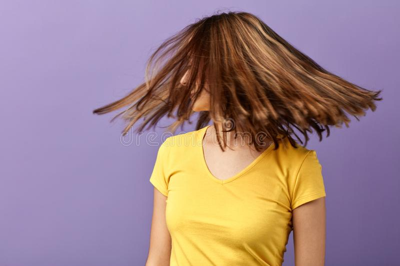 Young woman in stylish casual clothes with hair motion on blue background. Close up portrait, hair care, healthy hair, close up portrait, wellness, wellbeing royalty free stock photos