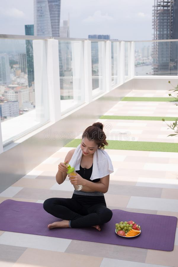 Young woman in stylish sportswear sitting and relaxing on the floor with plastic bottle of water after workout on the rooftop stock photos
