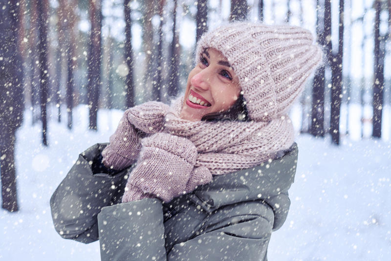 Young woman in stylish warm knitted cap and scarf looking upward royalty free stock photography