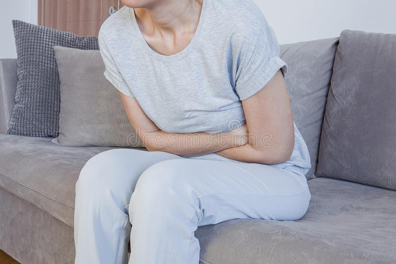 Stomach ache, women problems. Abdominal pain while sitting on bed at home. royalty free stock image