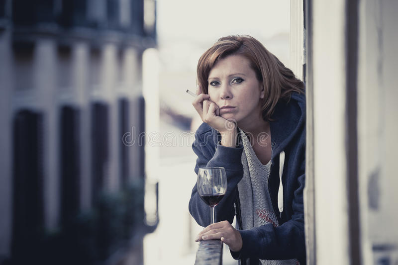 Young woman suffering depression drinking wine outdoors at the balcony royalty free stock photos