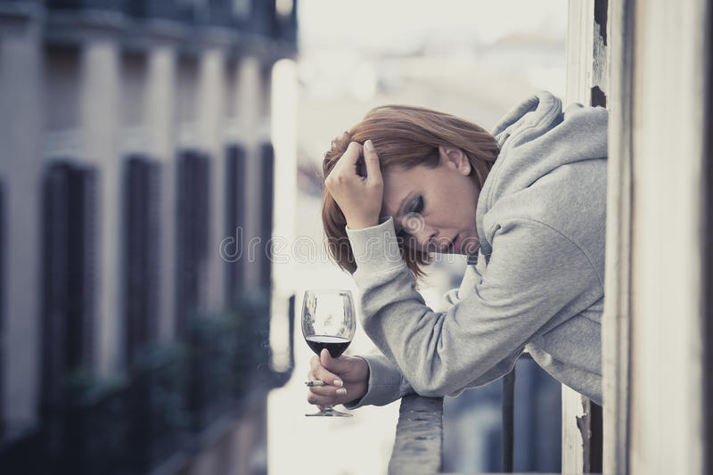 Young woman suffering depression drinking wine outdoors at the balcony. Young attractive woman suffering depression smoking and drinking wine in stress outdoors stock images