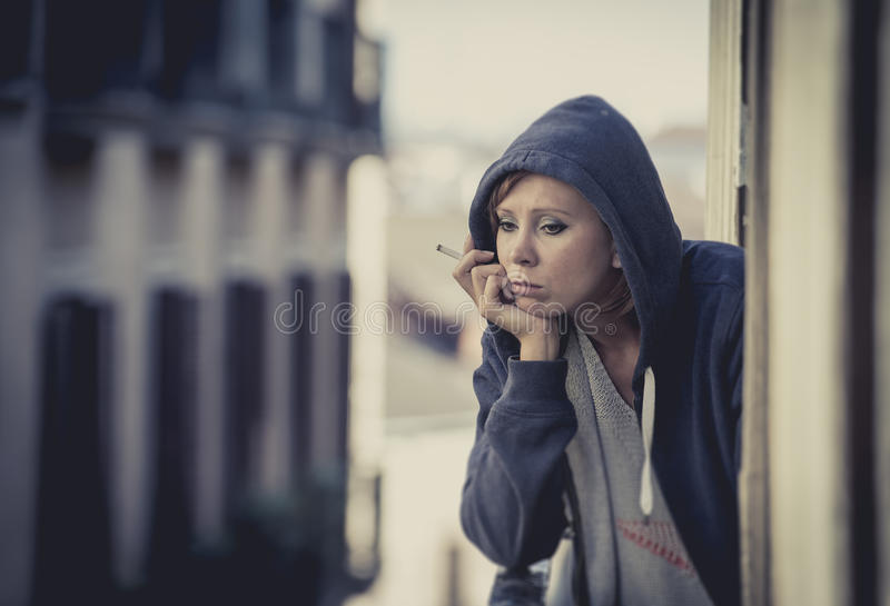 Young woman suffering depression and stress outdoors at the balcony. Young attractive woman suffering depression and smoking in stress outdoors at home balcony stock photos
