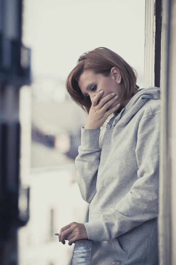 Young woman suffering depression and stress outdoors at the balcony. Young attractive woman suffering depression and smoking in stress outdoors at home balcony stock photo