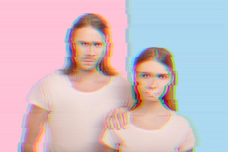 Young woman suffering from domestic violence and her husband looking angry royalty free stock image