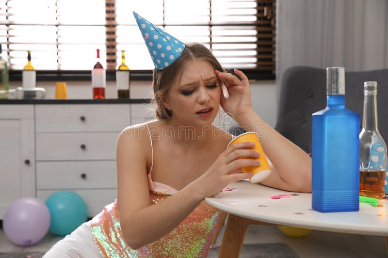 Young woman suffering from hangover in messy room. After party royalty free stock photos