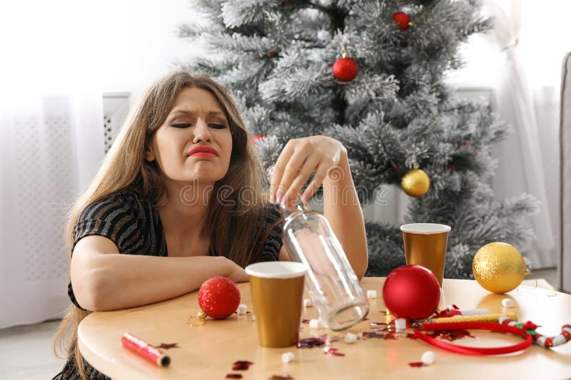 Young woman suffering from hangover at table after New Year party royalty free stock images
