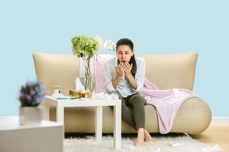 Young woman suffering from hausehold dust or seasonal allergy. Sneezing in the napkin and sitting surrounded by used napkins on the floor and sofa. Taking stock images