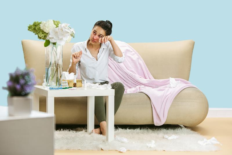 Young woman suffering from hausehold dust or seasonal allergy. Sneezing in the napkin and sitting surrounded by used napkins on the floor and sofa. Taking stock image