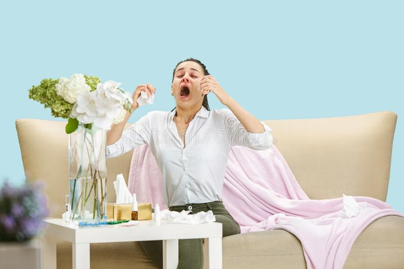 Young woman suffering from hausehold dust or seasonal allergy. Sneezing in the napkin and sitting surrounded by used napkins on the floor and sofa. Taking royalty free stock photo