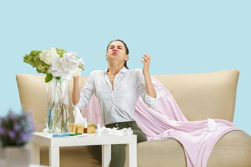 Young woman suffering from hausehold dust or seasonal allergy. Sneezing in the napkin and sitting surrounded by used napkins on the floor and sofa. Taking royalty free stock image