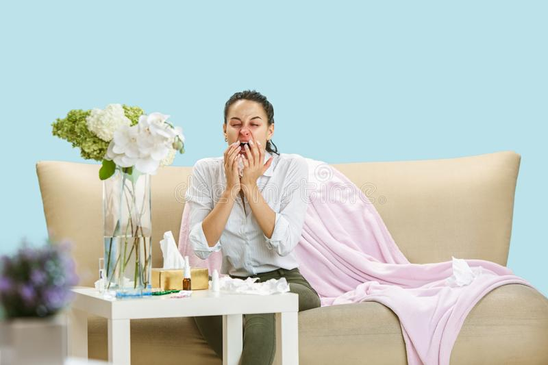 Young woman suffering from hausehold dust or seasonal allergy. Sneezing in the napkin and sitting surrounded by used napkins on the floor and sofa. Taking stock photos