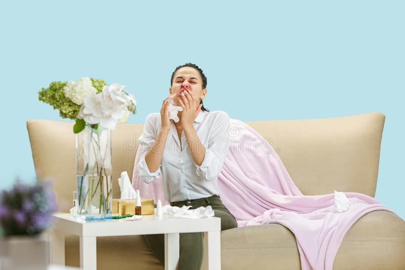 Young woman suffering from hausehold dust or seasonal allergy. Sneezing in the napkin and sitting surrounded by used napkins on the floor and sofa. Taking stock photo