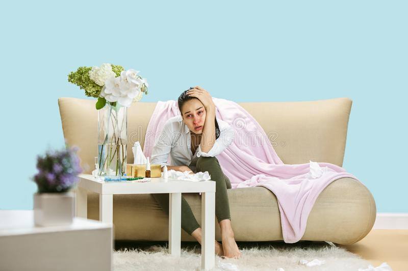 Young woman suffering from hausehold dust or seasonal allergy. Sneezing in the napkin and sitting surrounded by used napkins on the floor and sofa. Taking royalty free stock images