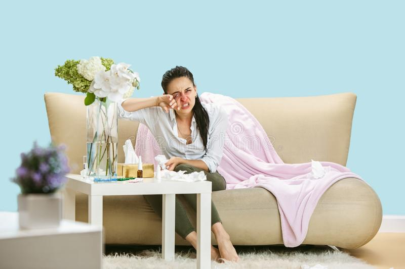 Young woman suffering from hausehold dust or seasonal allergy. Sneezing in the napkin and sitting surrounded by used napkins on the floor and sofa. Taking royalty free stock photos