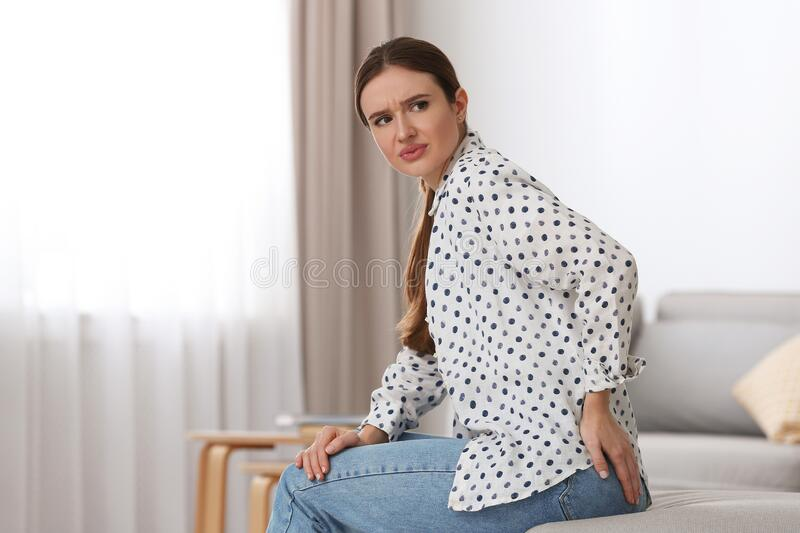 Young woman suffering from hemorrhoid . Space for text royalty free stock images