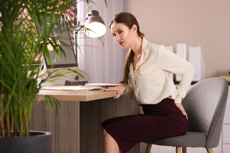 Young woman suffering from hemorrhoid at workplace royalty free stock images