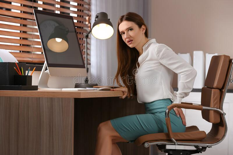 Young woman suffering from hemorrhoid at workplace stock images