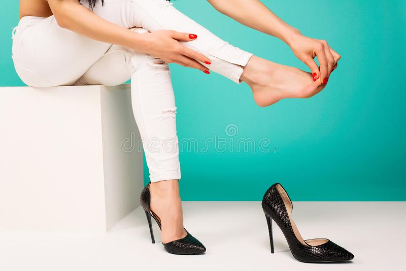 Young woman suffering from leg pain massaging toes because of uncomfortable shoes stock photography