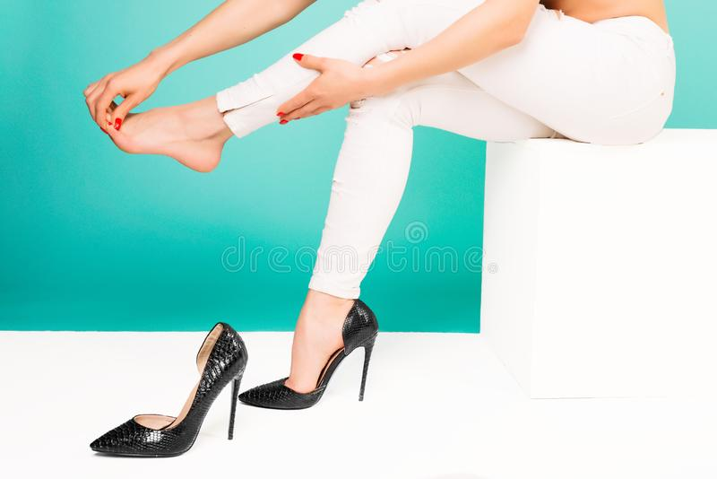 Young woman suffering from leg pain massaging toes because of uncomfortable shoes stock photos