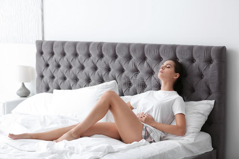 Young woman suffering from menstrual cramps at home stock images