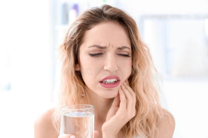 Young woman suffering from indoors. Young woman suffering from toothache indoors stock photo