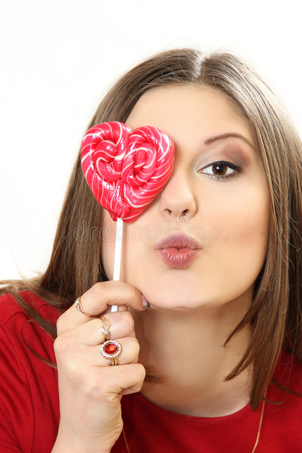 The young woman with sugar candy heart on a stick. White background royalty free stock photography