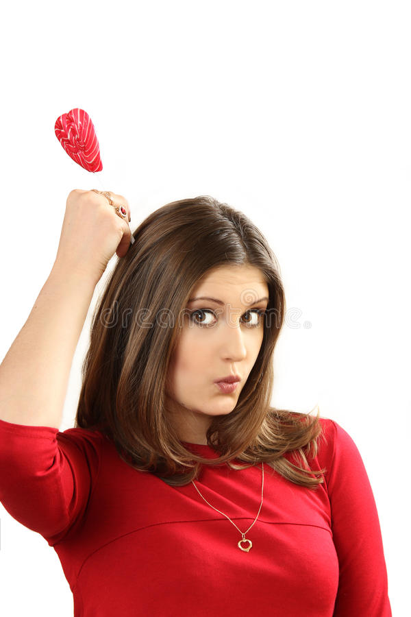 The young woman with sugar candy heart on a stick. White background stock photography