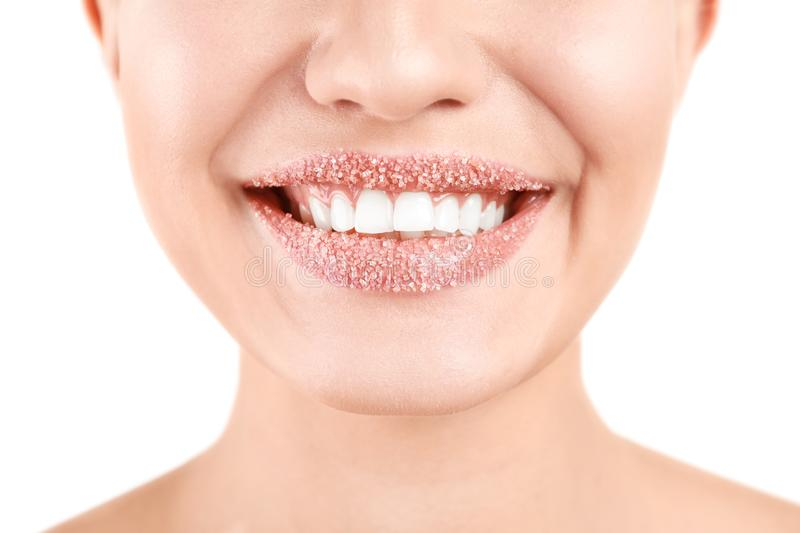 Young woman with sugar scrub on lips against white, closeup. Young woman with sugar scrub on lips against white background, closeup stock image