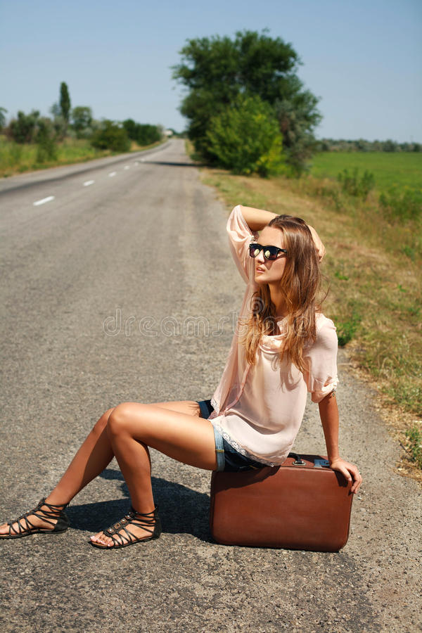 Young woman with suitcase hitchhiking on road in countryside. Young woman in the summer with a suitcase hitchhiking on the road in the countryside stock photos