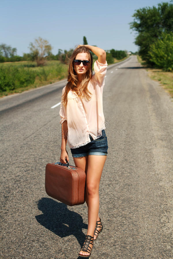Young woman with suitcase hitchhiking on road in countryside. Young woman in the summer with a suitcase hitchhiking on the road in the countryside royalty free stock photos