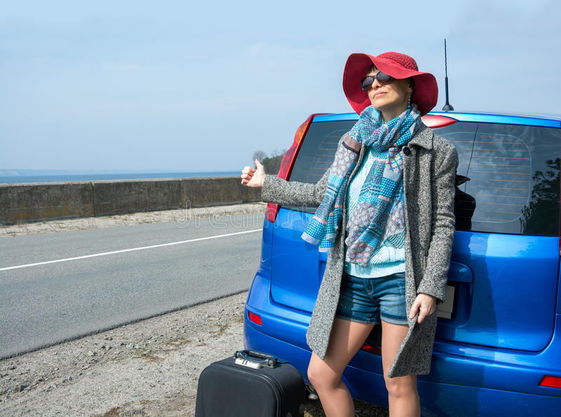 Young woman with a suitcase is hitchhiking on road near the sea. Pointing her thumb up royalty free stock photography