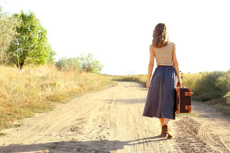 Young woman with suitcase walking along road royalty free stock image
