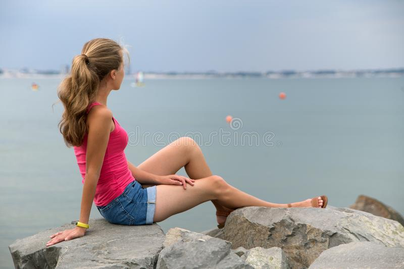 Young woman in summer clothes sitting on big boulders on sea shore looking on horizon royalty free stock photography