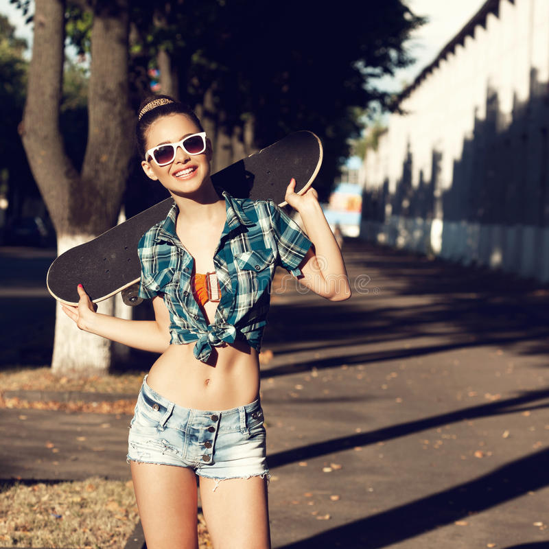 Young woman in summer dress. Trendy young girl in summer dress with skateboard. Outdoors. Urban lifestyle shot royalty free stock photos