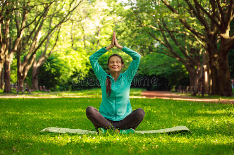 Young woman in summer park doing yoga with closed eyes stock photo