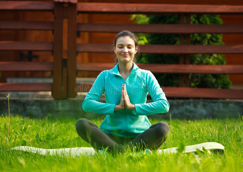 Young woman in summer park doing yoga with closed eyes royalty free stock image