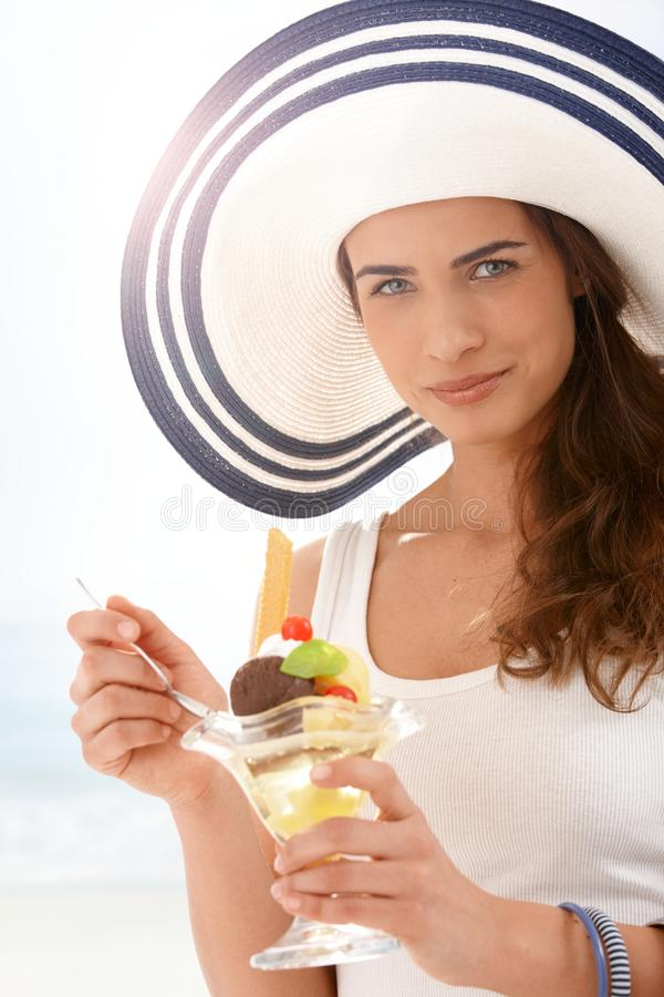 Young woman in summer straw eating icecream stock images