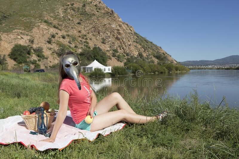 Young woman is relaxing on the lake in antiplague mask royalty free stock image