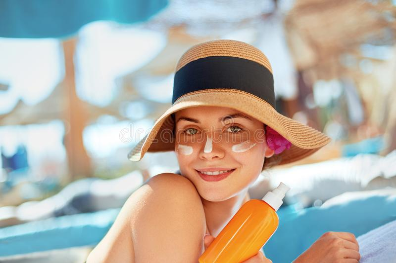 Young woman with sun cream on face holding sunscreen bottle on the beach. Female in hat applying moisturizing lotion on skin.  stock photo
