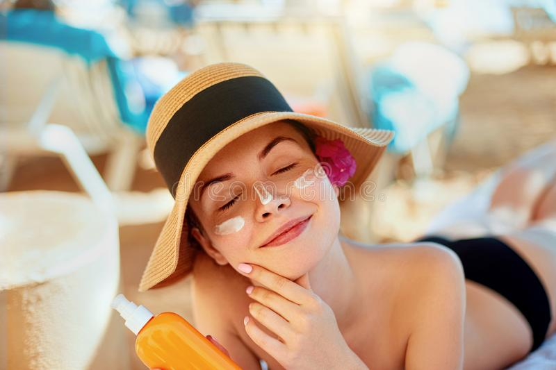 Young woman with sun cream on face holding sunscren bottle on the beach. Female in hat applying moisturizing lotion stock image