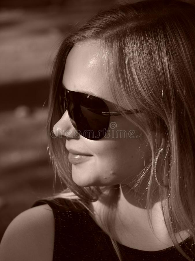 Young woman with sun glasses in sepia royalty free stock images