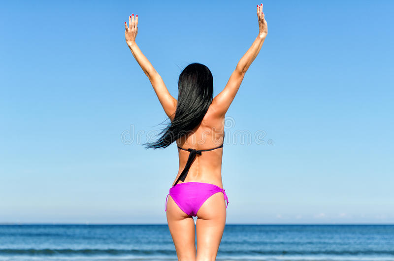 Young woman sunbathes. At the beach. From the back royalty free stock images