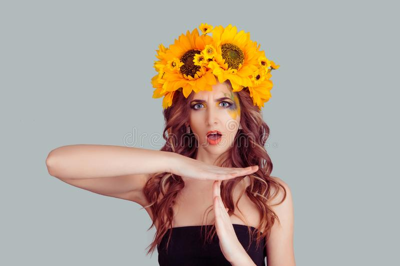 Woman in sunflowers floral crown showing time out hand gesture stock photos