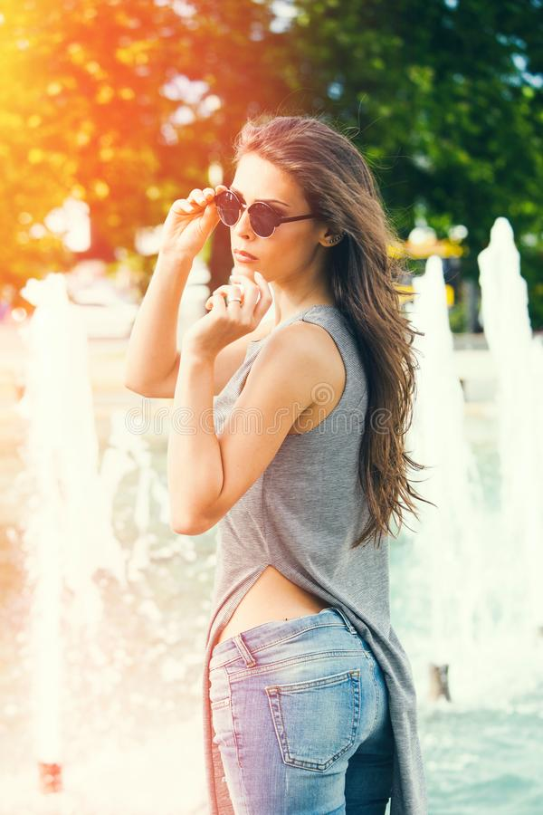 Young woman with sunglasses in blue jeans summer day in city stock photos