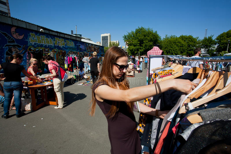Young woman in sunglasses chooses second hand dress stock images