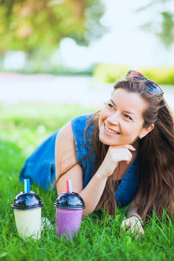 Young woman with sunglasses drink juicy tasty milkshakes on green lawn grass. Happy female model with two glasses of smoothie. Vertical shot stock images