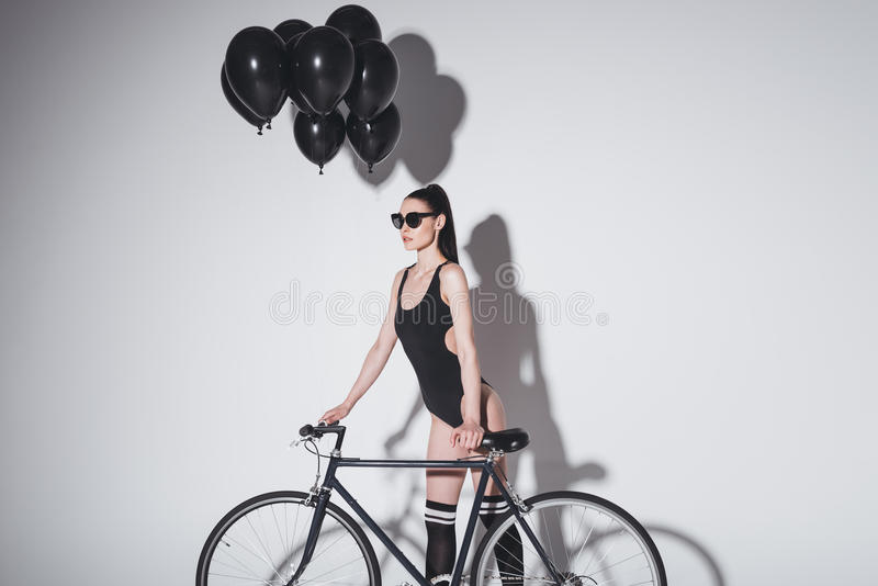 Young woman in sunglasses and fashionable swimsuit posing with bicycle and balloons in studio royalty free stock photo