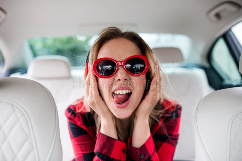 Young woman with sunglasses and headphones sitting in car, having fun. stock photo