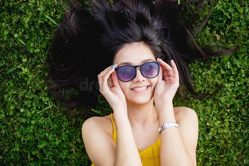 Young woman in sunglasses lying on a green lawn and smiling, top view stock photography